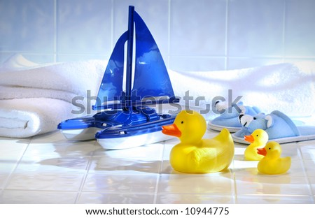 Toys with white towels on bathroom floor - stock photo