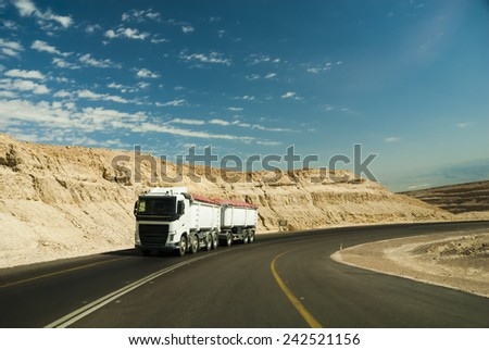 Trac driving on desert road. - stock photo
