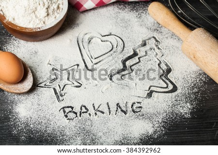 Trace of baking dish for Christmas cookies:star, heart, tree on wooden table with flour,rolling pin for cookies and gingerbread, accessories for baking, christmas time - stock photo