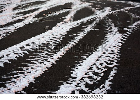 Traces of snow from the car on asphalt