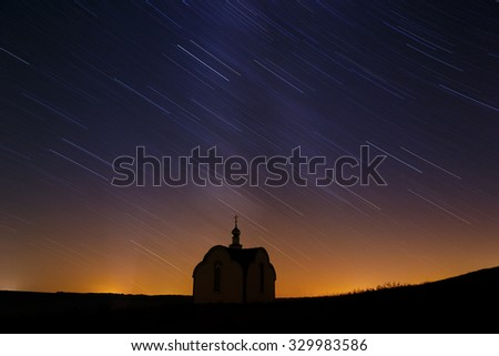 Traces of the stars in the night sky over the Orthodox church in Russia. - stock photo
