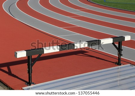 Track and athlete hurdling field - stock photo