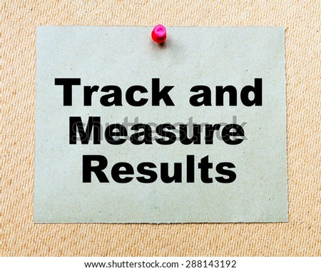 Track And Measure Results written on paper note pinned with red thumbtack on wooden board. Business conceptual Image - stock photo