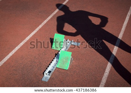 Track athlete casting shadow on starting blocks at the starting line of a race on a red running track - stock photo