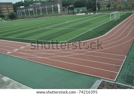 track fields with green grass in the middle