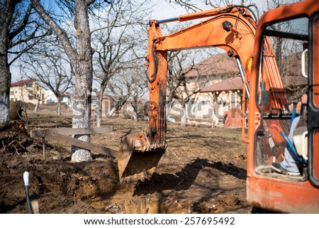 track-type loader excavator digging house foundation - stock photo