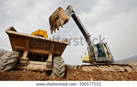 tracked excavator loading the material in a truck - stock photo