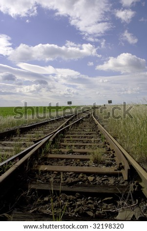 Tracks and switch surrounded by grass and signs