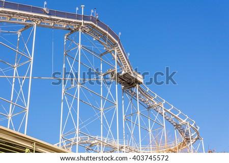 tracks of Roller coaster against blue sky. - stock photo