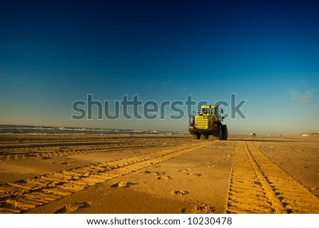 tracks on the beach with a bulldozer in the distance - stock photo