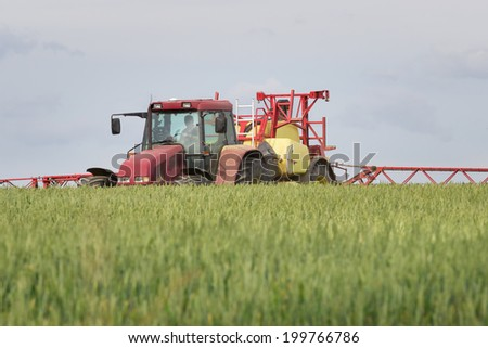 Tractor and pesticides in the grain field - stock photo