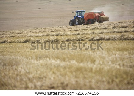 Tractor baling straw in sunny, rural field