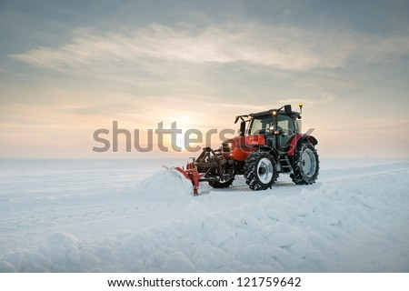 Tractor cleaning snow in field