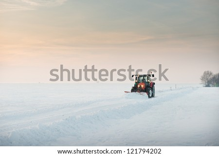 Tractor cleaning snow in field - stock photo