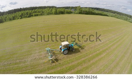 Tractor collect hay on field at summer sunny day. Aerial view videoframe - stock photo