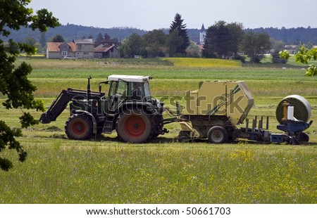 Tractor collecting hay on the fields.