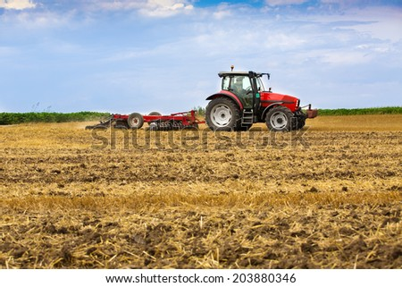Tractor cultivating wheat stubble field, crop residue.