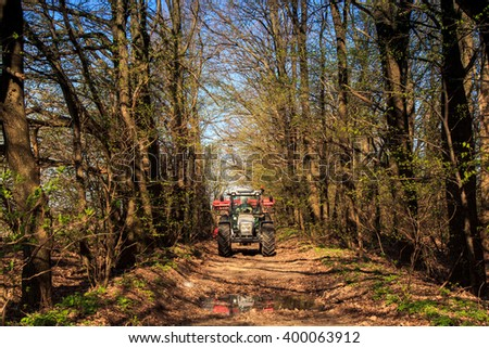 tractor cultivator on big wheels on natural soil road in spring forest against blue sky - stock photo