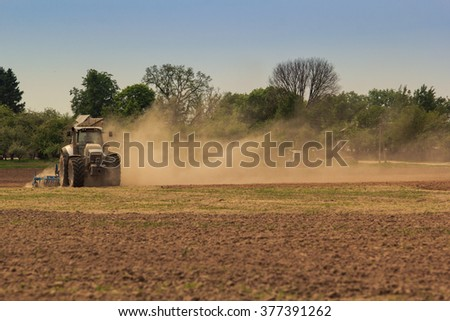 tractor cultivator on big wheels operates on ploughed field raises great dust in spring against wheat field and forest - stock photo