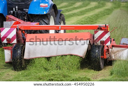 Tractor cutting grass hay with harvesting machine in the field. Detail