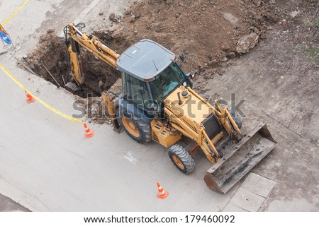 tractor excavator digging the ground to stop the  leaking in water pipes - stock photo
