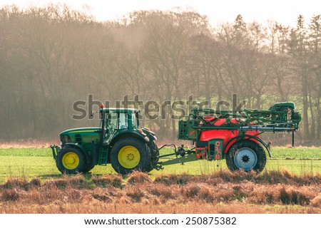 Tractor ferilizing a field in early spring - stock photo