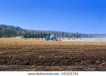 Tractor for agricultural work in a plowed field. - stock photo