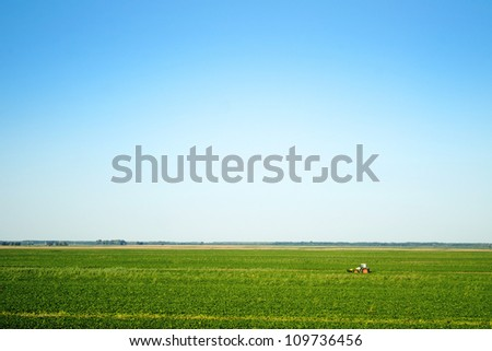 Tractor harvesting green field in the distance - stock photo