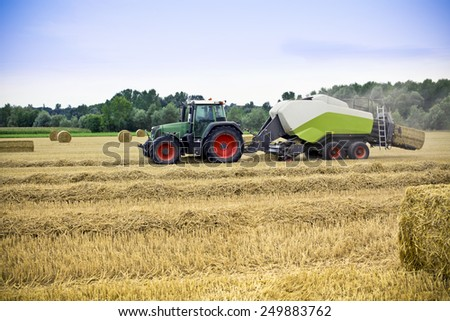 Tractor harvests wheat on a field - stock photo