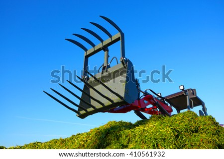 Tractor in a farmer field.The production of forage and hay.The background of agriculture industry - stock photo