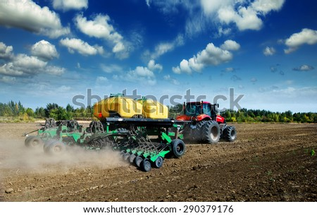 tractor in a field plowing - stock photo