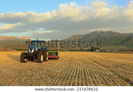 Tractor in a fresh cut hay field, Utah, USA. - stock photo