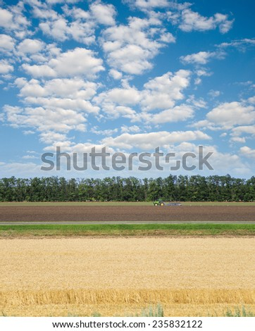 Tractor in field crops processing - stock photo