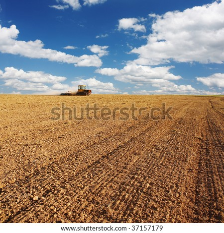 Tractor in field under blue sky with clouds - stock photo