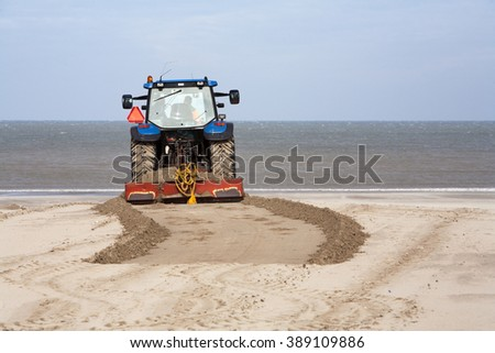 Tractor leveling the beach - stock photo