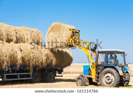 Tractor loading hay bales on truck trailer during agricultural works - stock photo