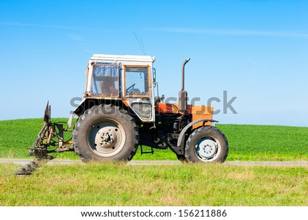 Tractor machine with grass cutter mowing lawn along road during machinery landscaping works - stock photo