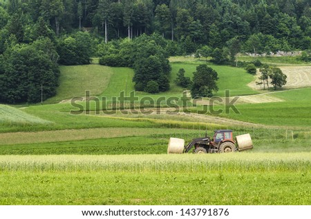 Tractor moving hay bales with forest in background - stock photo