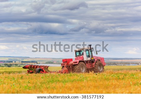 Tractor on field beneath cloudy sky in summer day - stock photo