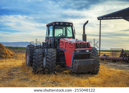 Tractor on the Field, sunset. Tractor is specifically designed to deliver a high tractive effort at slow speeds, for the purposes of hauling a trailer or machinery used in agriculture or construction. - stock photo