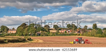 Tractor planting seeds in the autumn, countryside village in background - stock photo