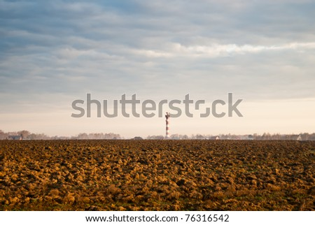 tractor plowed field in the spring morning - stock photo