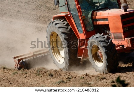 tractor plowing field  - stock photo