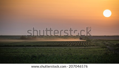 tractor plowing field at dusk - stock photo