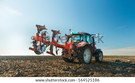 Tractor plowing field in autumn - stock photo