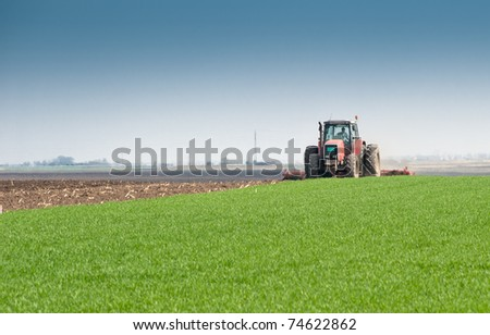 Tractor plowing the fields in spring - stock photo