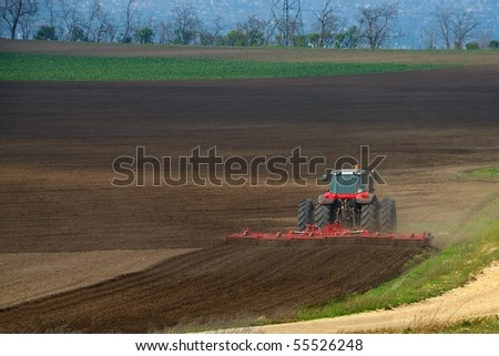 Tractor plowing the fields in the countryside - stock photo