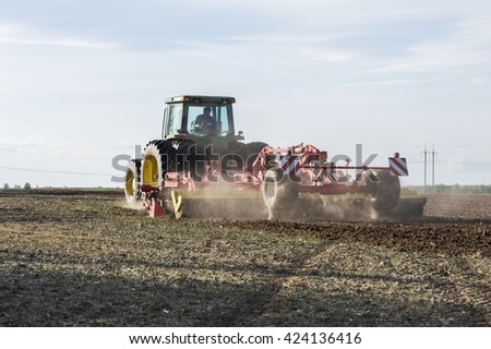 tractor plowing the land in a field - stock photo