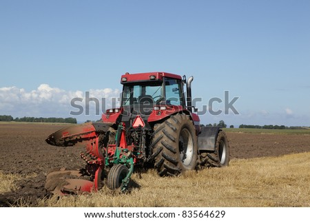 Tractor plowing the soil at harvest time. - stock photo