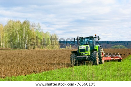 Tractor plows a field in the spring accompanied by rooks Tractor plows a field in the spring accompanied by rooks - stock photo